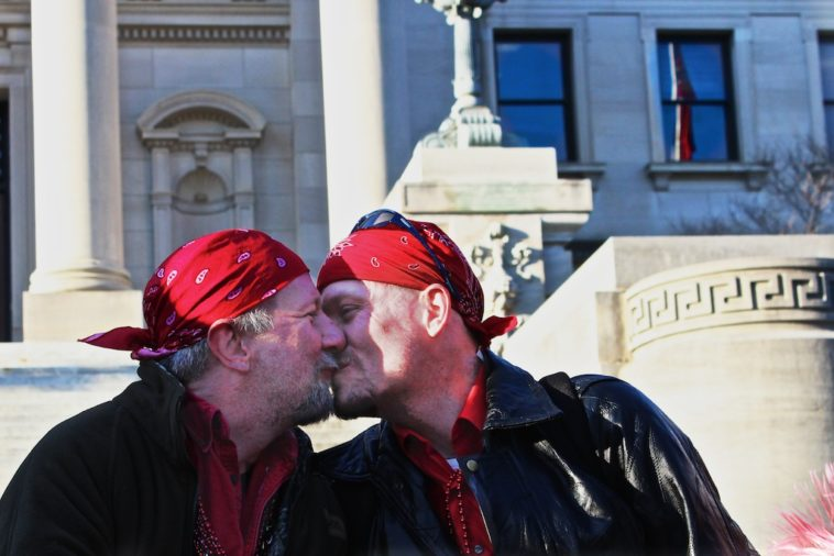 Two bikers kiss on the steps of the Mississippi capitol