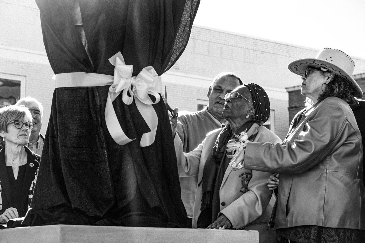 Ellie Dahmer cuts the ribbon that held the veil over the statue of her husband. Photo by Ashton Pittman.
