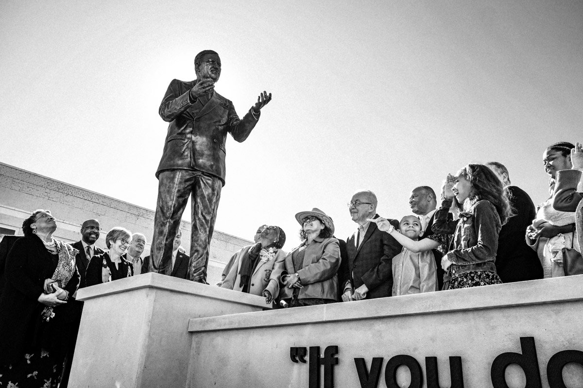 "Ellie Dahmer (front right at the base of the statue) looks up joyfully after pulling the veil off a statue of her husband, Vernon Dahmer, a civil rights activist who died while saving her and their children when the Ku Klux Klan firebombed their home in 1966. Forrest County held the unveiling ceremony for the new statue on Jan. 6, 2020. Gathered around her, family members exclaim, ""It looks like him!"" Photo by Ashton Pittman."